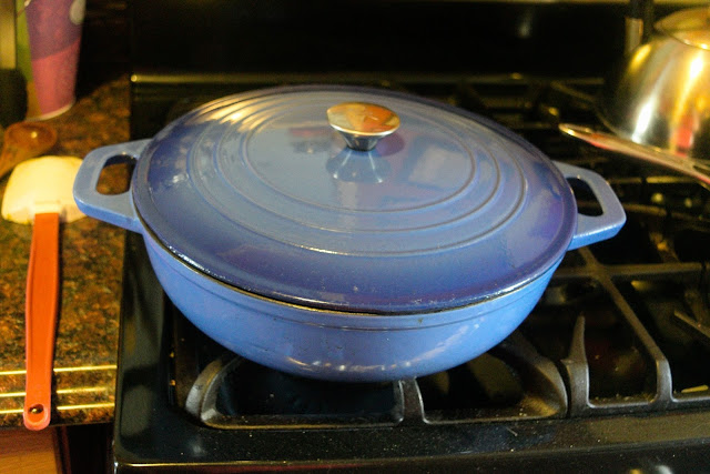 The dutch oven, on the stove, with the lid on it, allowing the vegetables to steam.