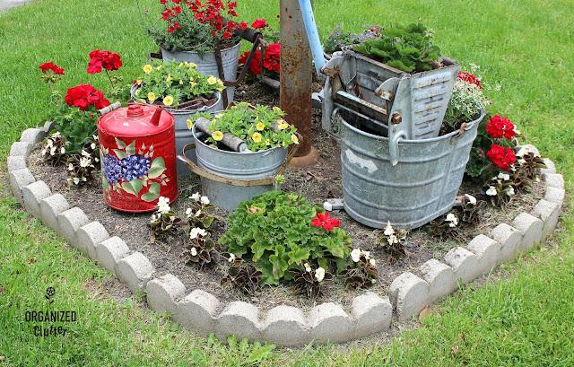 A Gathering of Mop Buckets in a Small Junk Garden #galvanizedplanter #galvanized #containergarden #junkgarden #annuals #redgeraniums