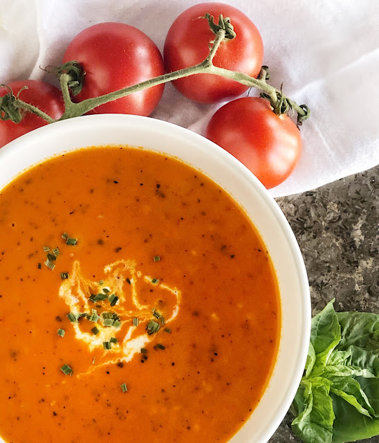Roasted Tomato Soup in a white bowl with tomatoes and basil on the side