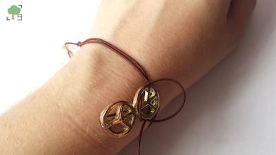 pacyfizm, jeden koralik beżowy, sznurek brąz i złoto