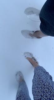 Twee paar blote voeten in de sneeuw