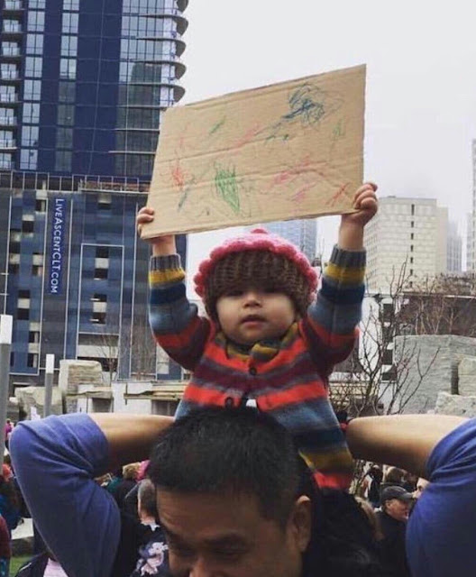 Child holding up a sign that she drew