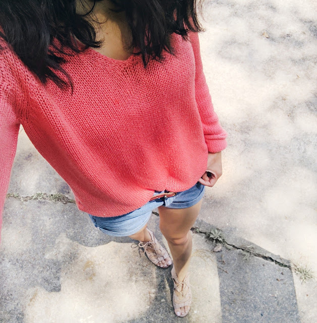 bright coral knit sweater and denim shorts