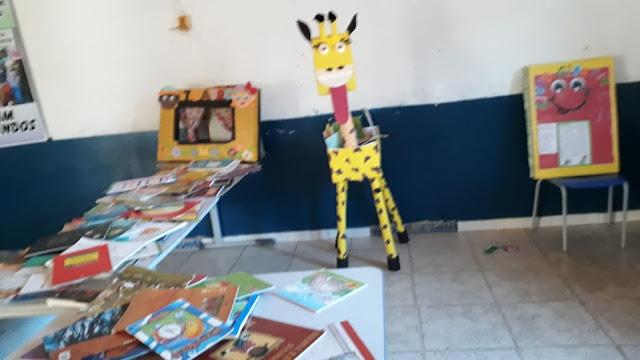 Cantinho da leitura lindamente decorado com girafa gigante de material reciclável
