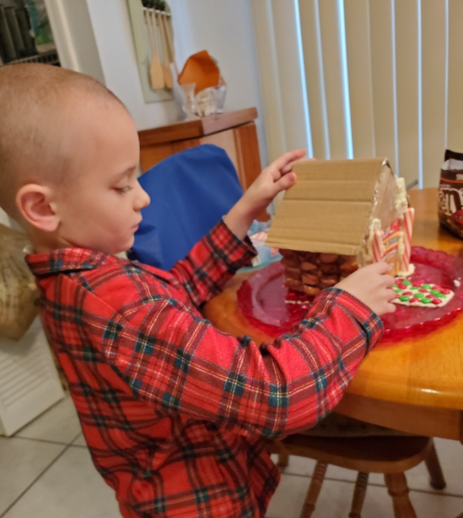 this is my grandson making a Christmas candy house he is six years old