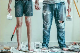 Couple holding hands and brushes after repainting walls