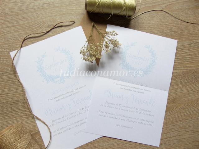 Un tarjetón de boda doblado con corona de laurel y letras manuscritas de estilo clásico