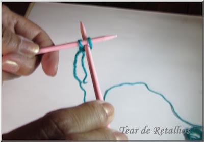 Foto mostrando a agulha direita entre os dois pontos da agulha esquerda para iniciar a execução da técnica à inglesa de montagem da base do tricô. Cable Cast on.