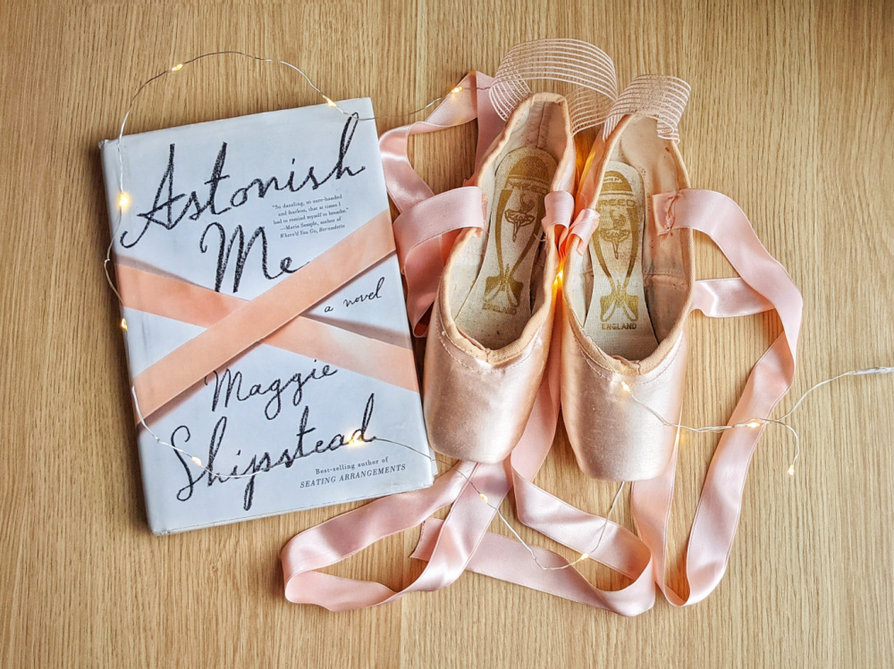 Novel Astonish Me by Maggie Shipstead, fairy lights, and pointe shoes.