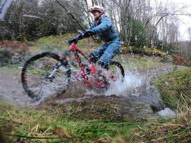 woman in dirtlej dirtsuit pro splashing through puddle on mountain bike