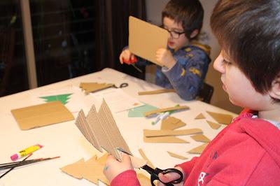 duas crianças a cortar o desenho de duas árvores de Natal em cartão