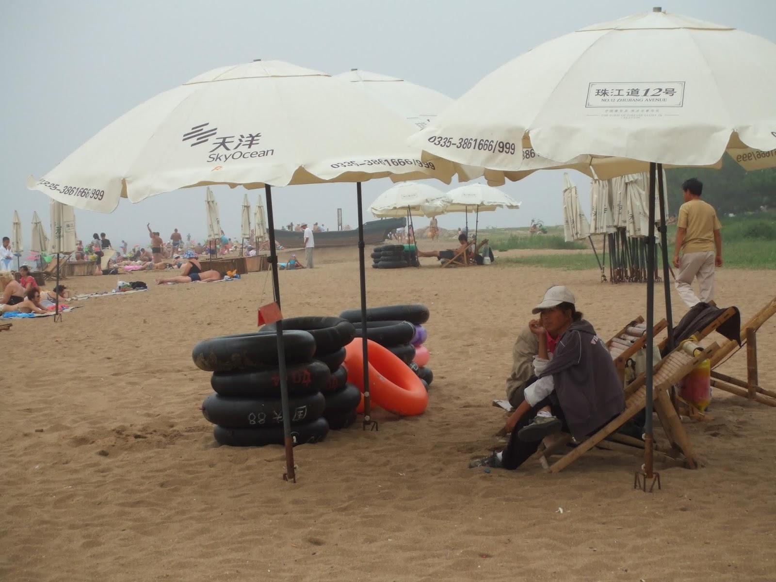 schwarze Schwimmreifen, glber Sand, weiße Sonnenschirme, Menschen