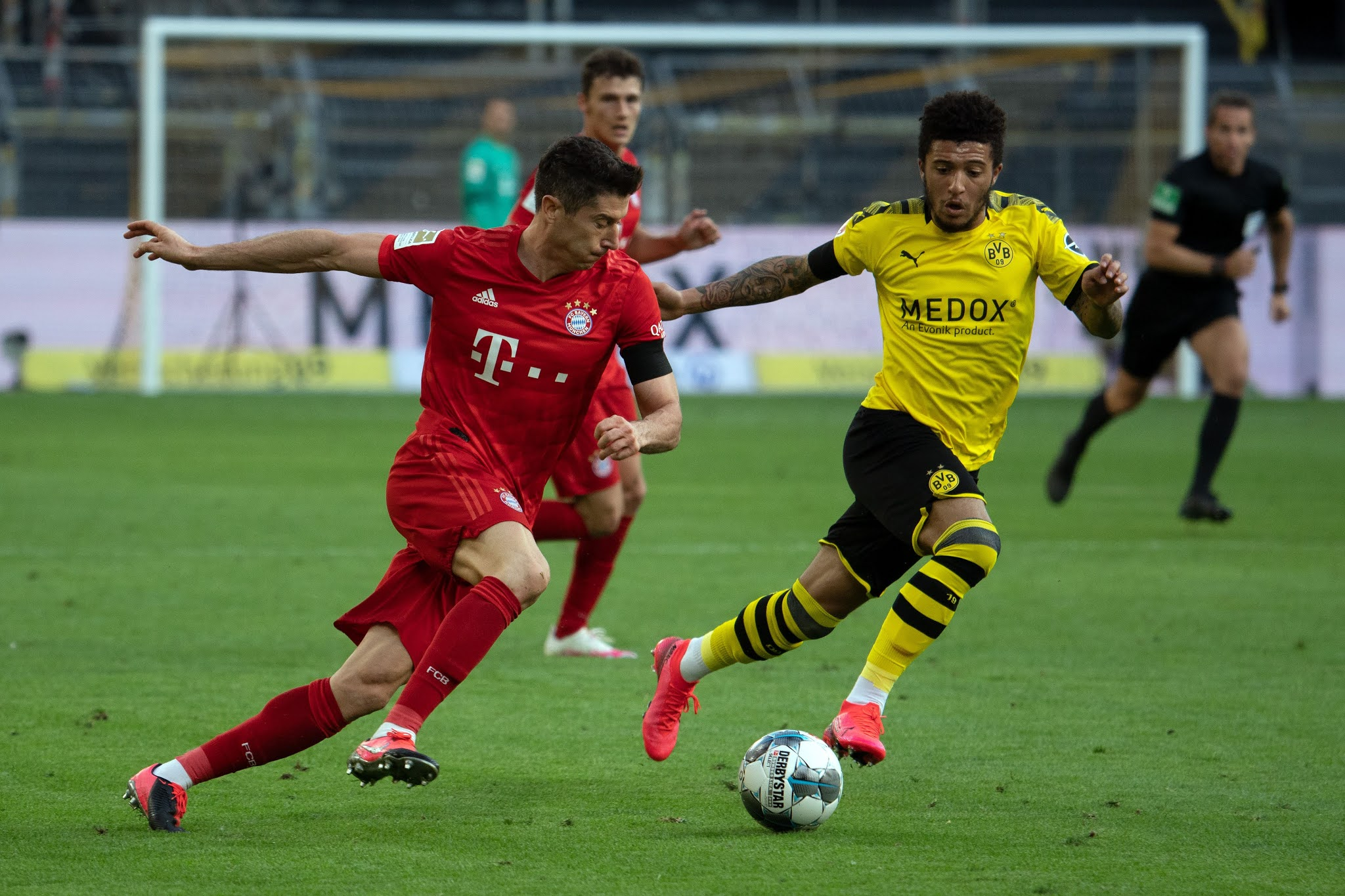 Robert Lewandowski e Jadon Sancho no último encontro entre Bayern e Dortmund pela Bundesliga (Photo by FEDERICO GAMBARINI/POOL/AFP via Getty Images)