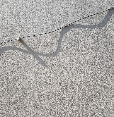 A Minimalist Photo of the long shadow of a metal wire on a textured white wall shot by Samsung Galaxy S6 Smart Phone