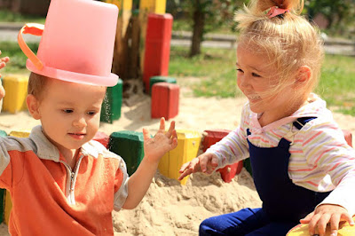 Boys-Little-girls-playing-with-Bucket-wearing-on-his-head