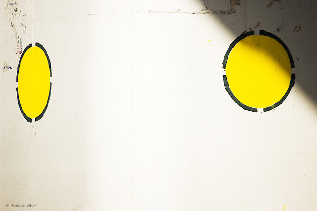 A minimalist photo of Two yellow circles on the wall of an over-bridge. One of them being cut by a triangle formed by shadow.