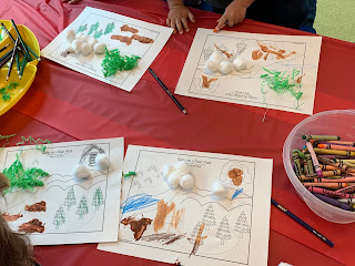 kids coloring and adding sensory paint and cotton balls to We're Going on a Bear Hunt sensory map outline