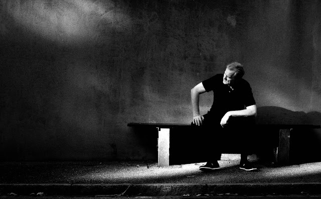 Man sitting on a bench in black and white.