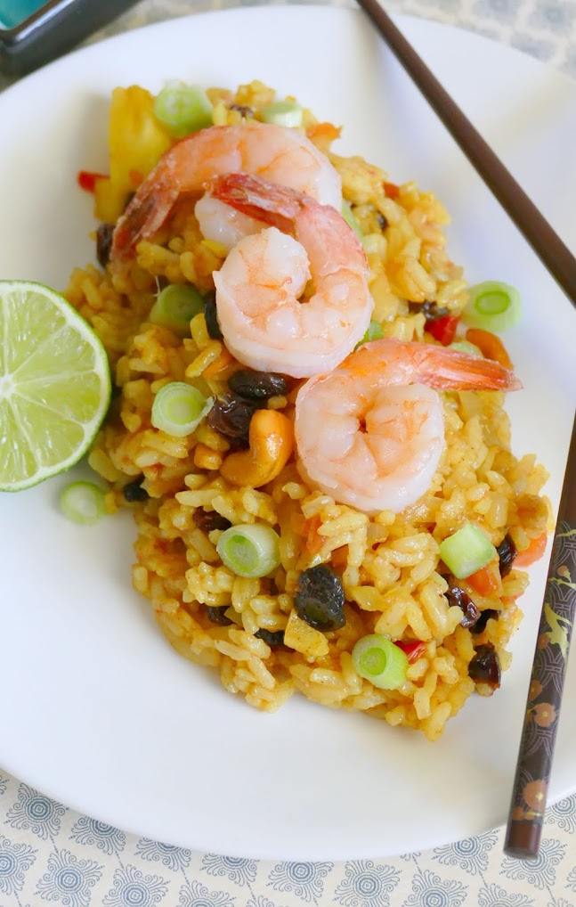 This easy 30 minute Shrimp Pineapple Fried Rice is delicious and such a great way to use leftover rice! This Thai inspired recipe gets it's flavors from pineapple, nuts, curry and raisins, along with vegetables and shrimp. Also great with chicken and so much better than takeout!