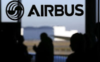 People are silhouetted past a logo of the Airbus Group during the Airbus annual news conference in Colomiers, near Toulouse January 13, 2015. (Credit: Reuters/Regis Duvignau) Click to Enlarge.