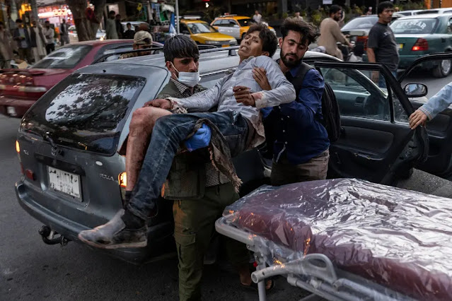 An injured person is carried on a stretcher outside a hospital in Kabul. Photo: New York Times