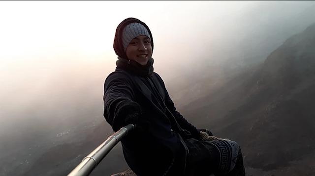 garoto tirando uma selfie em cima de uma montanha