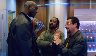 "Kevin Garnett (Kevin Garnett) and Demany (Lakeith Stanfield) discuss borrowing a rare stone containing black opals from Howard Ratner (Adam Sandler) in The Safdie Brothers' 2019 film ""Uncut Gems."""