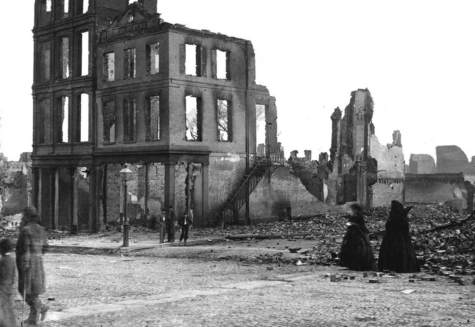 Residents walk through the ruins of Richmond, Virginia, in April of 1865. Richmond served as the capital of the Confederate States of America during the majority of the Civil War. After a long siege in 1865, with General Ulysses S. Grant's Union troops about to take the city, Confederate troops were ordered to evacuate, destroying bridges and burning supplies they they could not carry. A massive fire swept through Richmond, destroying large parts of the city. About one week after the evacuation of Richmond, Gen. Robert E. Lee surrendered to Grant in near Appomattox, Virginia, on April 9, 1865.