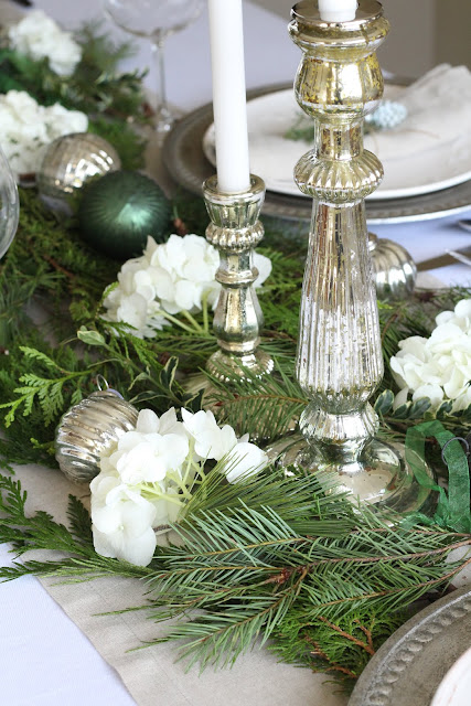 holiday tablescape with greens ornaments silver white green