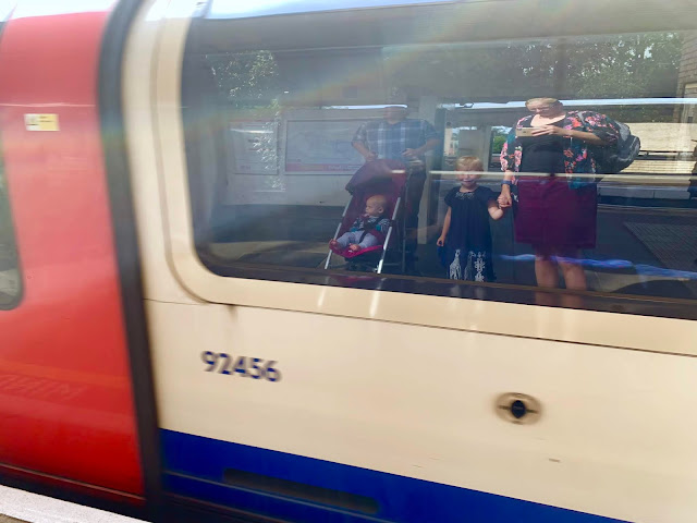 A tube train pulling into a station with the reflection of a family in the window