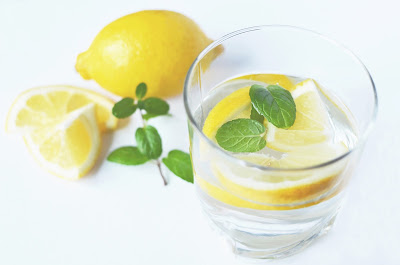 Full glass of water with lemon and mint, with whole lemon, lemon slices, and sprig of mint next to it