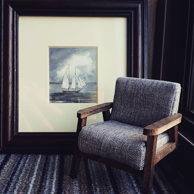 Small framed watercolour of a boat propped up against the wall. In front of it is a piece of carpet tile and a 1/12 scale modern miniature armchair in greys and browns.