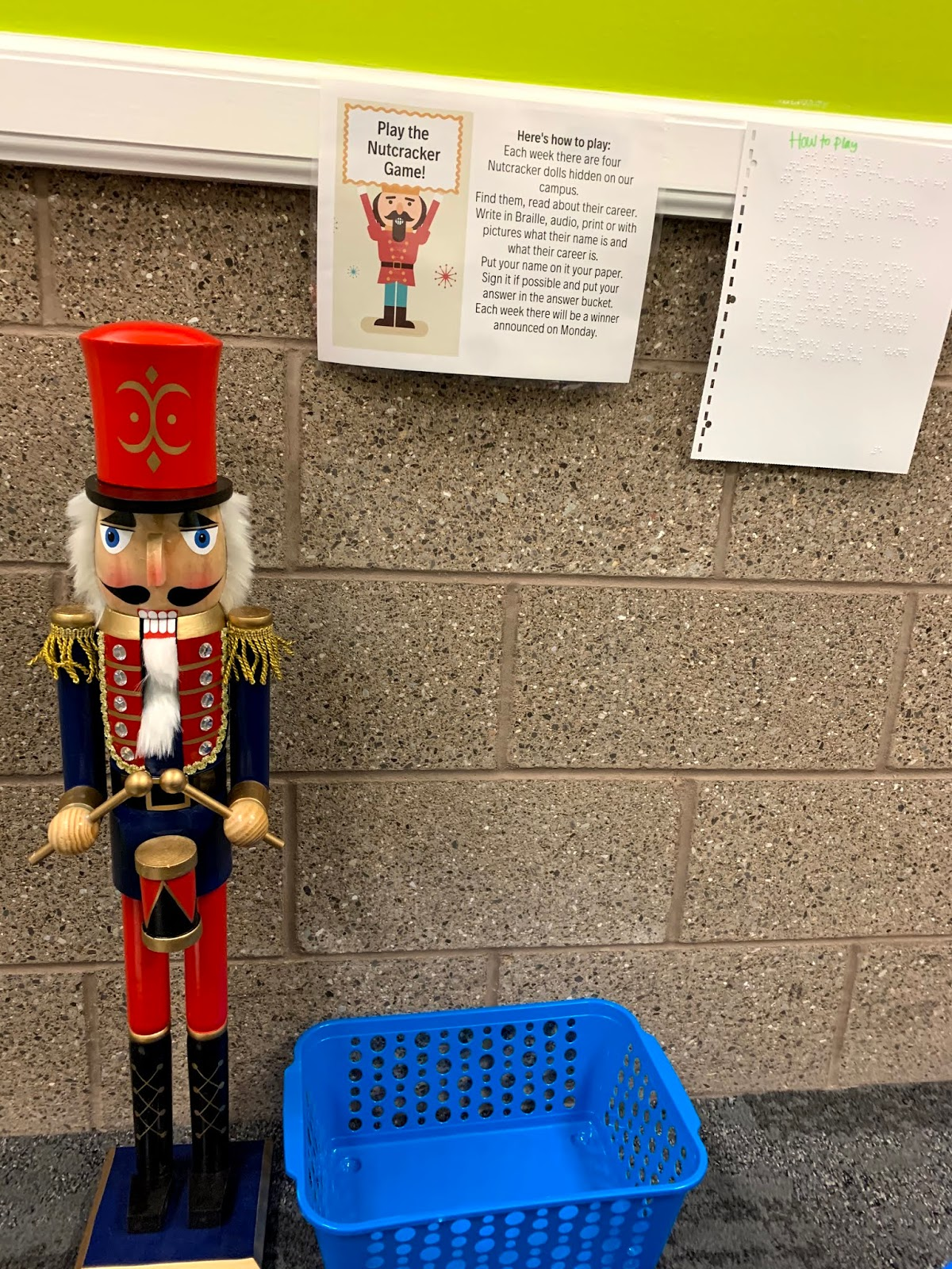 a large traditional Nutcracker doll with a basket and a game sign on how to play the game behind it.