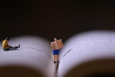 livro-com-um-homem-em-miniatura-lendo-e-outro-homem-sentado
