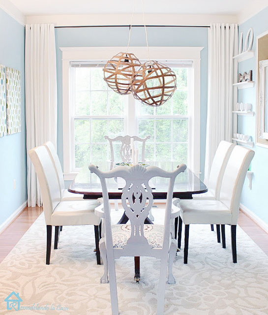 white and blue dining room facing a large window