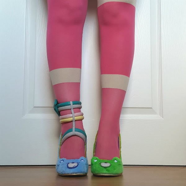 legs facing forward wearing bright pink tights and colourful care bears shoes