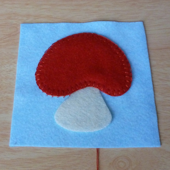 Hand stitched sewn red felt mushroom toadstool cap on blue background fabric