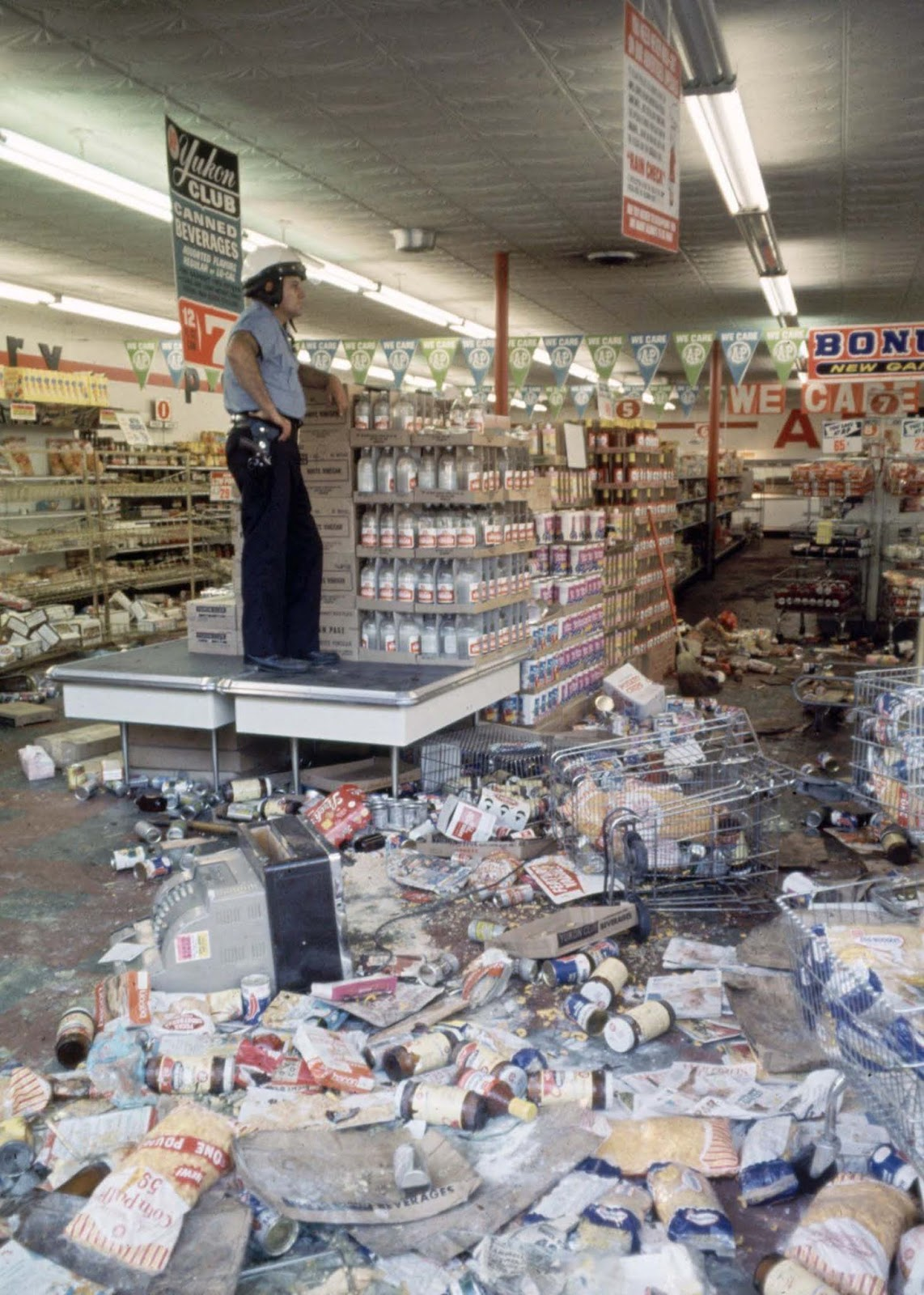 Detroit police officer standing guard over a grocery store, which was looted and damaged during the riot.