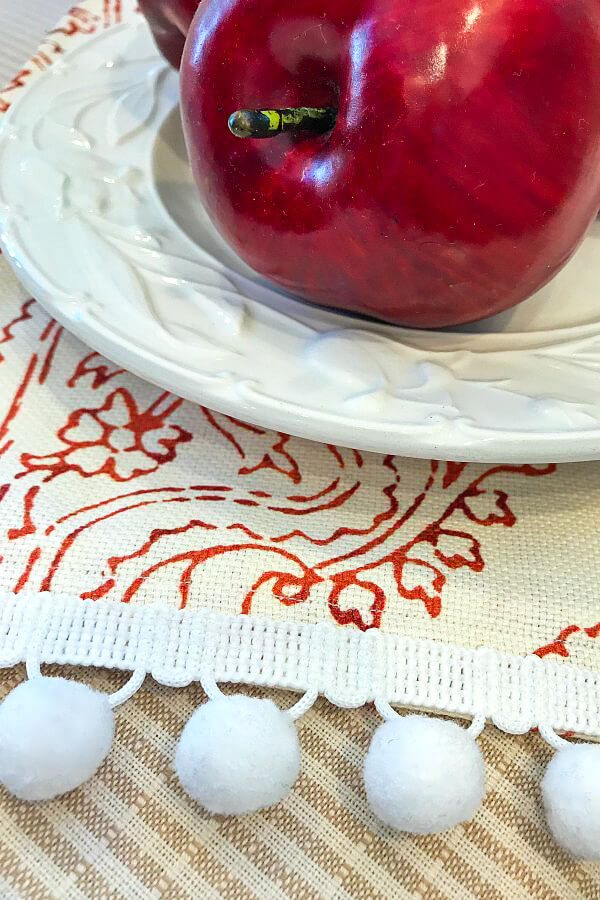 Apple on red plate and red fabric with ball fringe