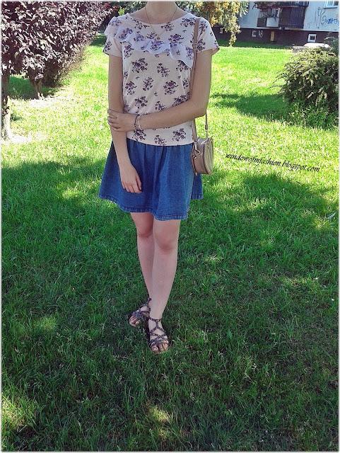 T-shirt z kwiatowym motywem i asymetryczną falbanką, jeansowa spódniczka, bransoletki z konikiem morskim oraz sterem, złoty medalik, sandały z ćwiekami, torebka-serce