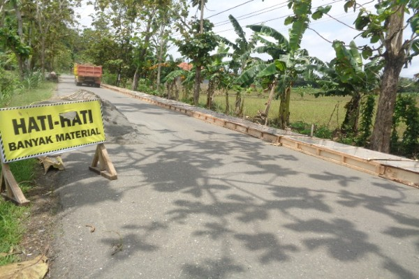 Rambu peringatan banyak material bangunan di jalan