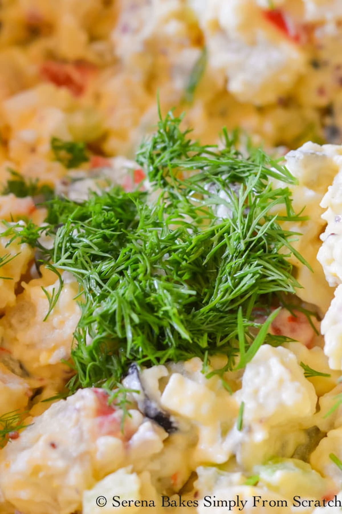 Fresh Chopped Dill added to Potato Salad with Olives in a large bowl.