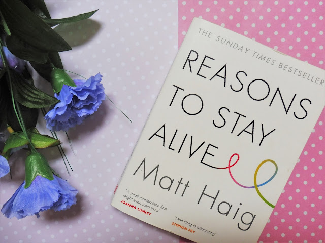 "A picture of the book ""Reasons To Say Alive"" with pink background and purple flowers"