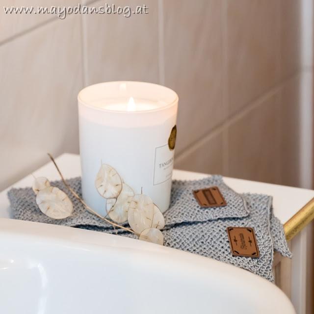 Gestrickte Handtücher mit Duftkerze im Badezimmer