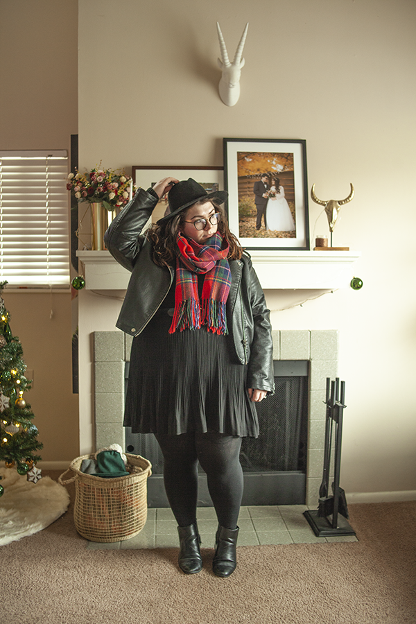 An outfit consisting of a wide brim black har, a red plaid scarf, a black faux leather moto jacket over a black sweater tucked into a black mini pleated skirt with black tights and ankle boots.