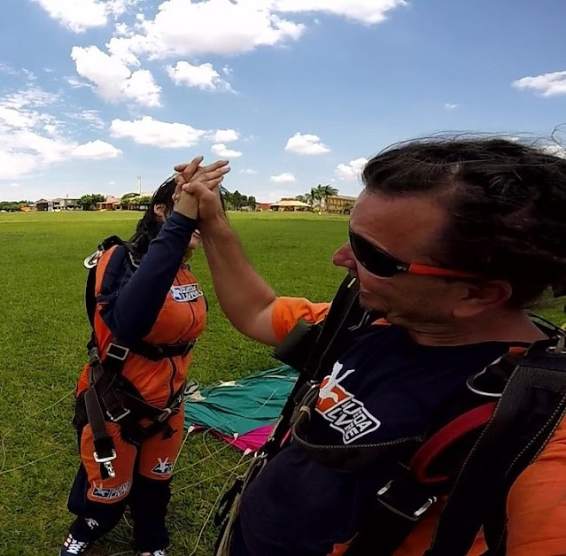 mulher e instrutor de paraquedismo dando as maos