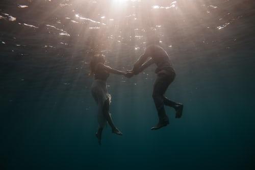 dwoje zakochanych w wodzie trzyma się za ręce