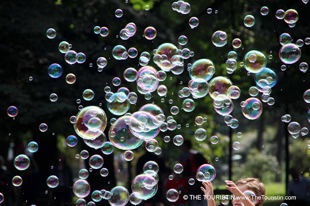 A mall boy reaching for hundreds of soap bubbles on a summer's day