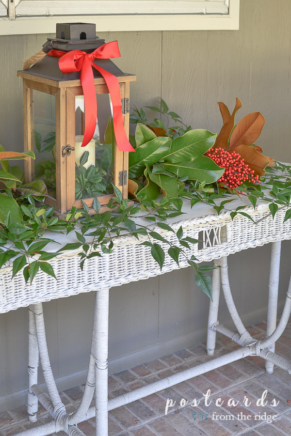 wooden lantern and greenery on vintage white wicker table on porch