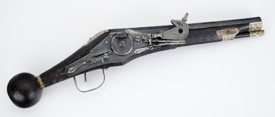 A gun with a wooden stock, in a shape somewhat similar to a modern rifle, but only a single short barrel. It is front-loading, with an elaborate wheeled mechanism controlled by the trigger (a clamp that would hold a piece of flint and a spring-loaded steel wheel that can be wound), and the rear ends in a sphere with ivory inlay.